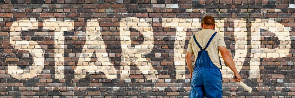 Un currante con mono está pintando sobre una pared STARTUP