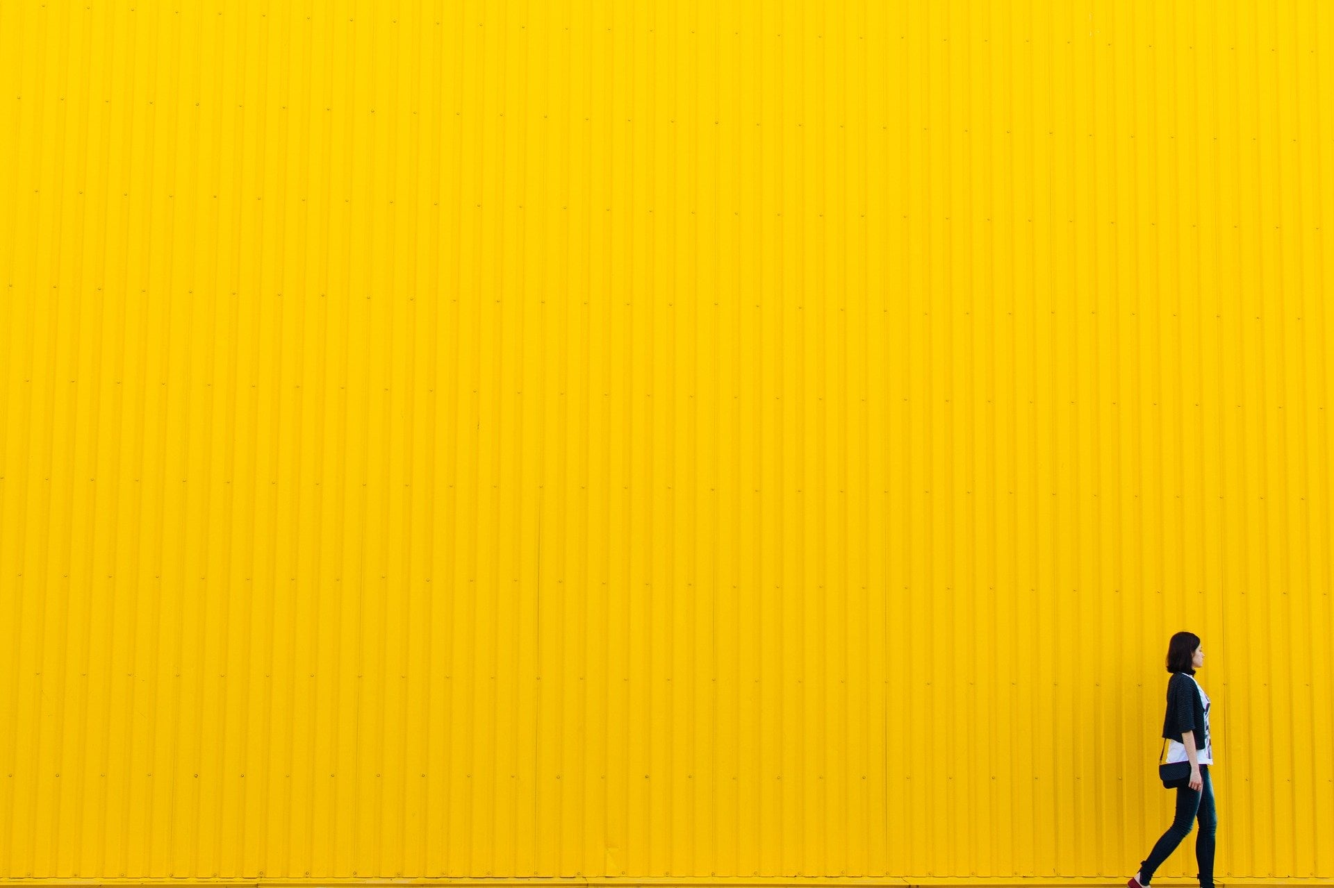 Persona caminando sobre una pared amarilla
